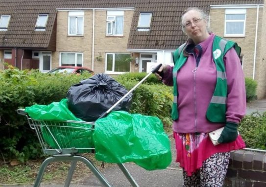 A lady holding a litter picker next to a shopping trolley with bin bags in it