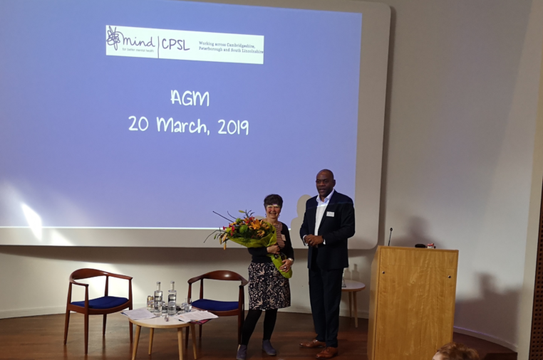 A black man and white woman holding flowers at the 2019 AGM