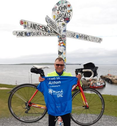 Aidan Joy holding his bike with a blue CPSL Mind tshirt in front of the John O Groats sign