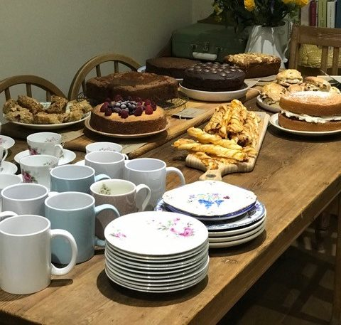 A wooden table with mugs, plates and cakes