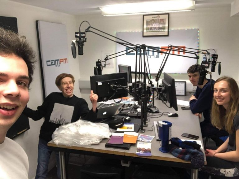 A group of men and a woman in the Cam FM radio studio