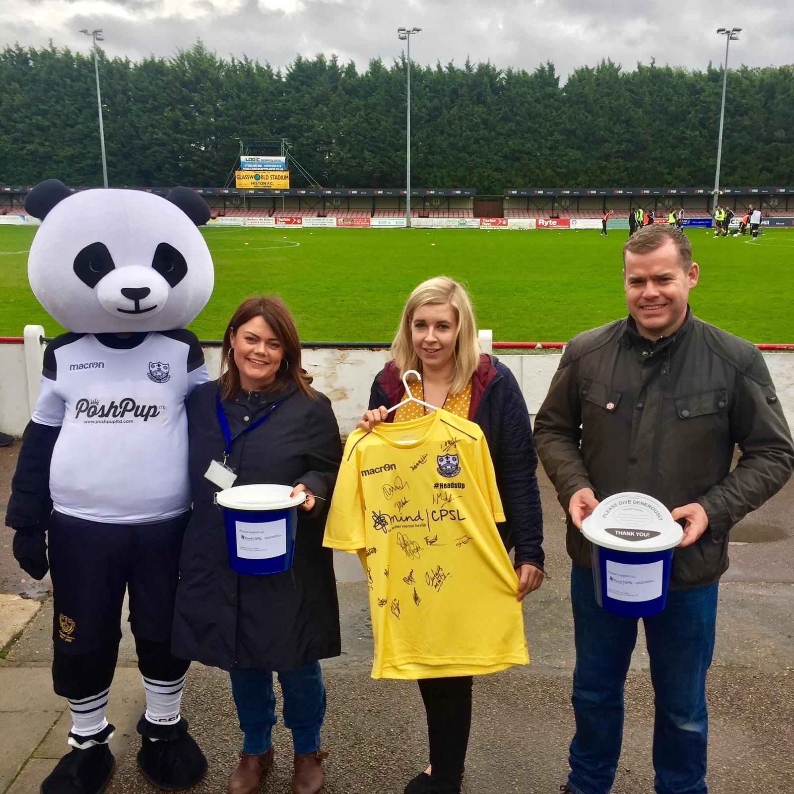 Two women and a man with a Panda mascot, signed football shirt and collection buckets in front of a football pitch