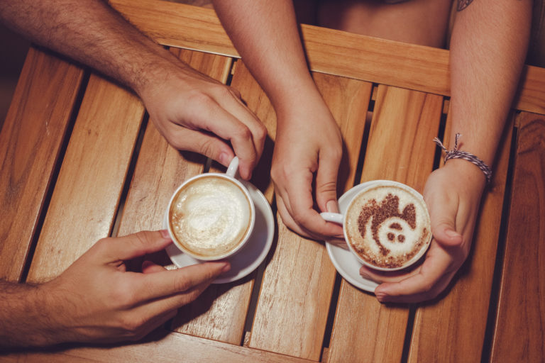 A wooden table with two people's hands holding coffee cups one has a smiley face design in the milk