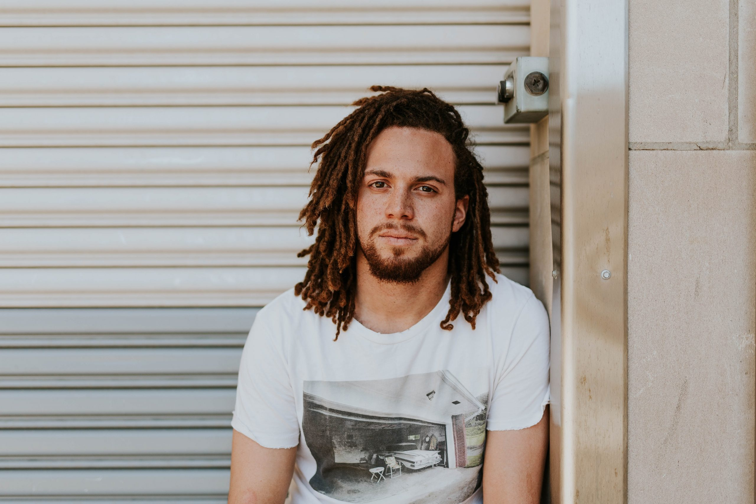 A man with dread locks and a white t shirt looking at the camera