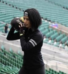 A dark haired lady wearing all black holding a weight on her shoulder in a sports stadium