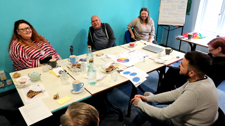Group of people sat at a table in a room with a blue wall