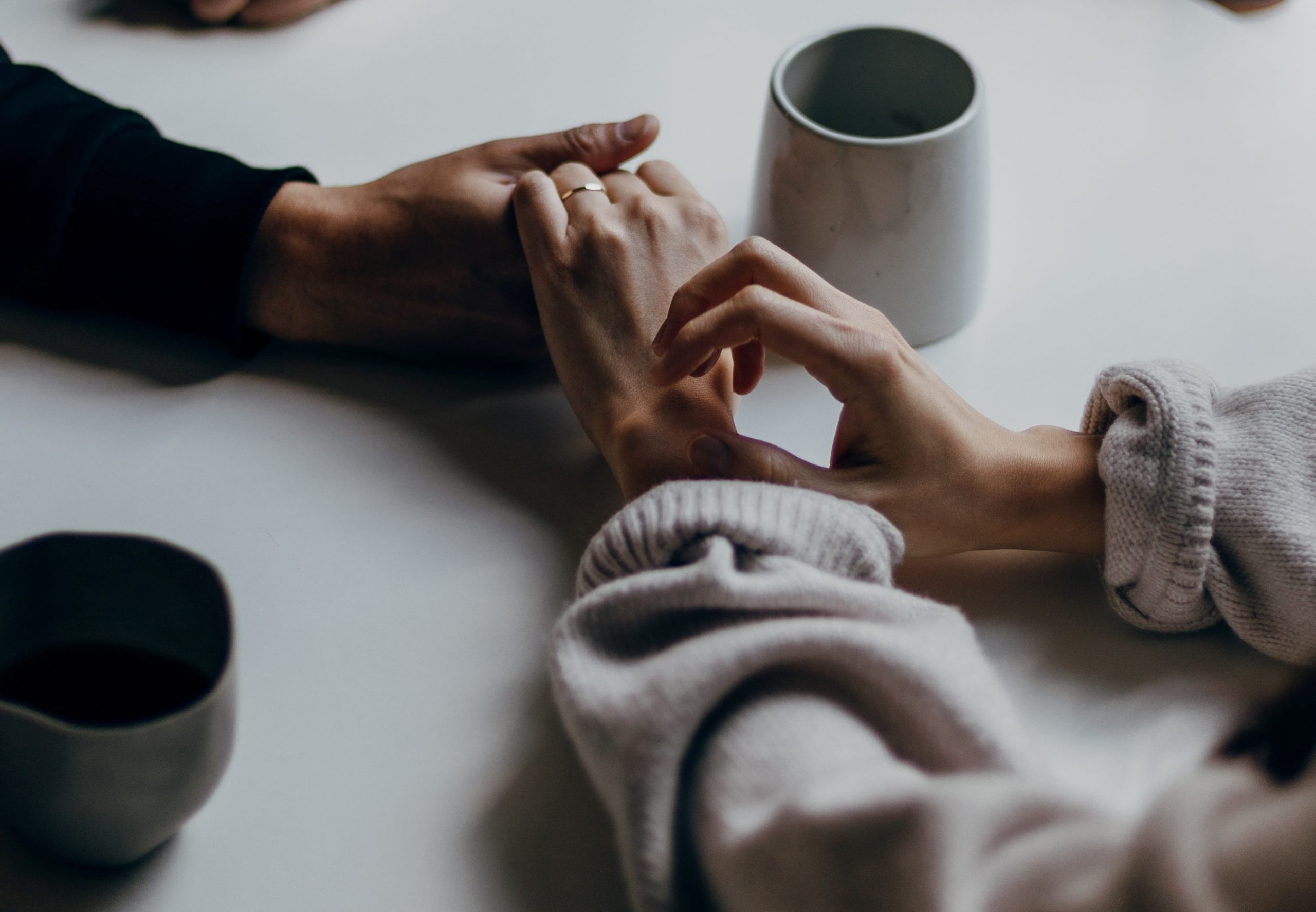 two people holding hands on a table with mugs on it