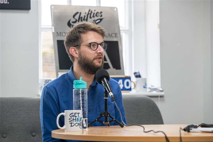 Man with glasses and a beard sat down speaking into a microphone