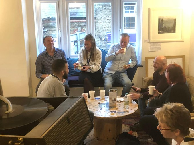 A group of men and women drinking hot drinks and talking