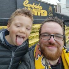 A little boy with his tongue out next to a man smiling at Cambridge United