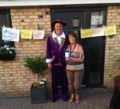 A man and woman in fancy dress in front of a front door with a washing line with signs saying CPSL Mind Mental Health Awareness Week