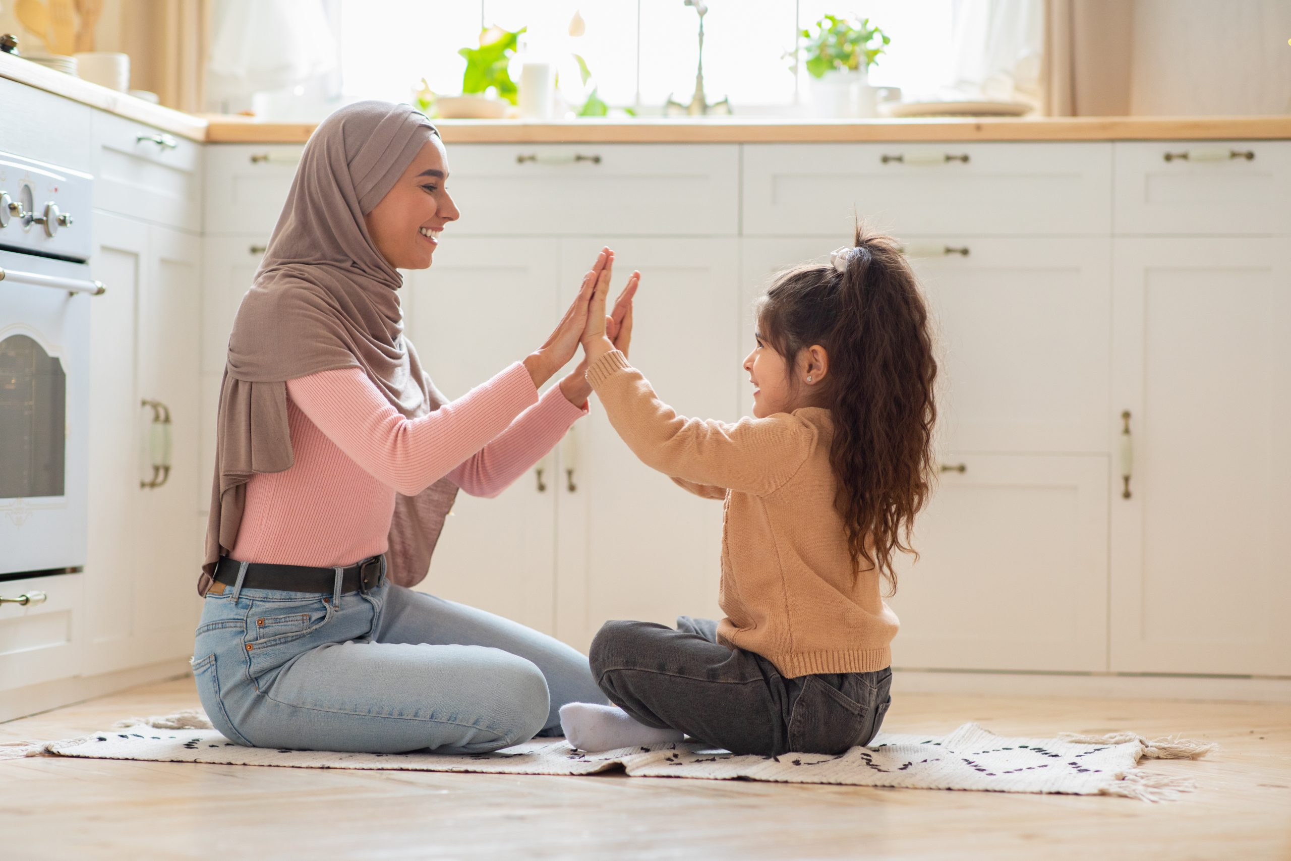 Happy muslim mum playing with her little daughter on floor in kitchen