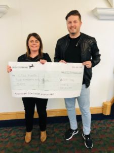 A man and a woman holding a cheque for CPSL Mind