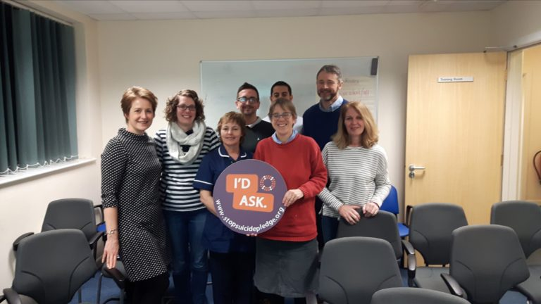 Group of people in a room with grey chairs holding a purple and orange I'd Ask Stop Suicide pledge sign