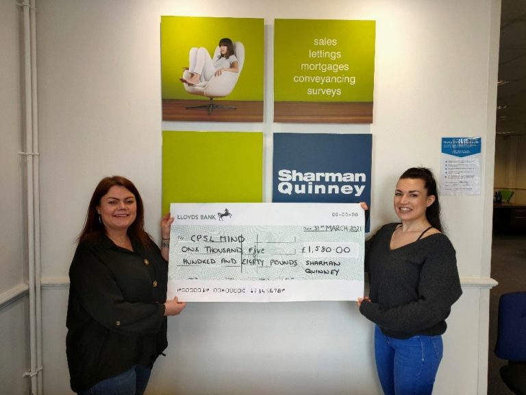 Two women in front of a Sharman Quinney sign holding a cheque for CPSL Mind for £1,580