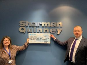 A woman and man in front of a Sharman Quinney sign holding a cheque for CPSL Mind