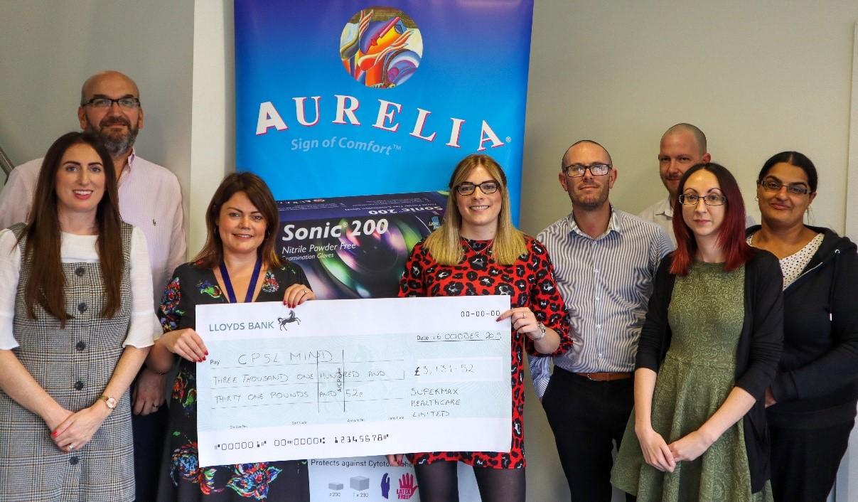A group of men and women holding a cheque for CPSL Mind in front of an Aurelia sign