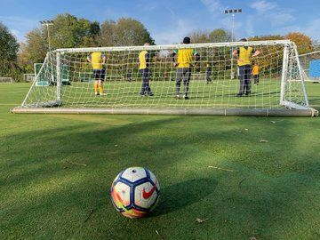 A football behind a football net with players in front of the net