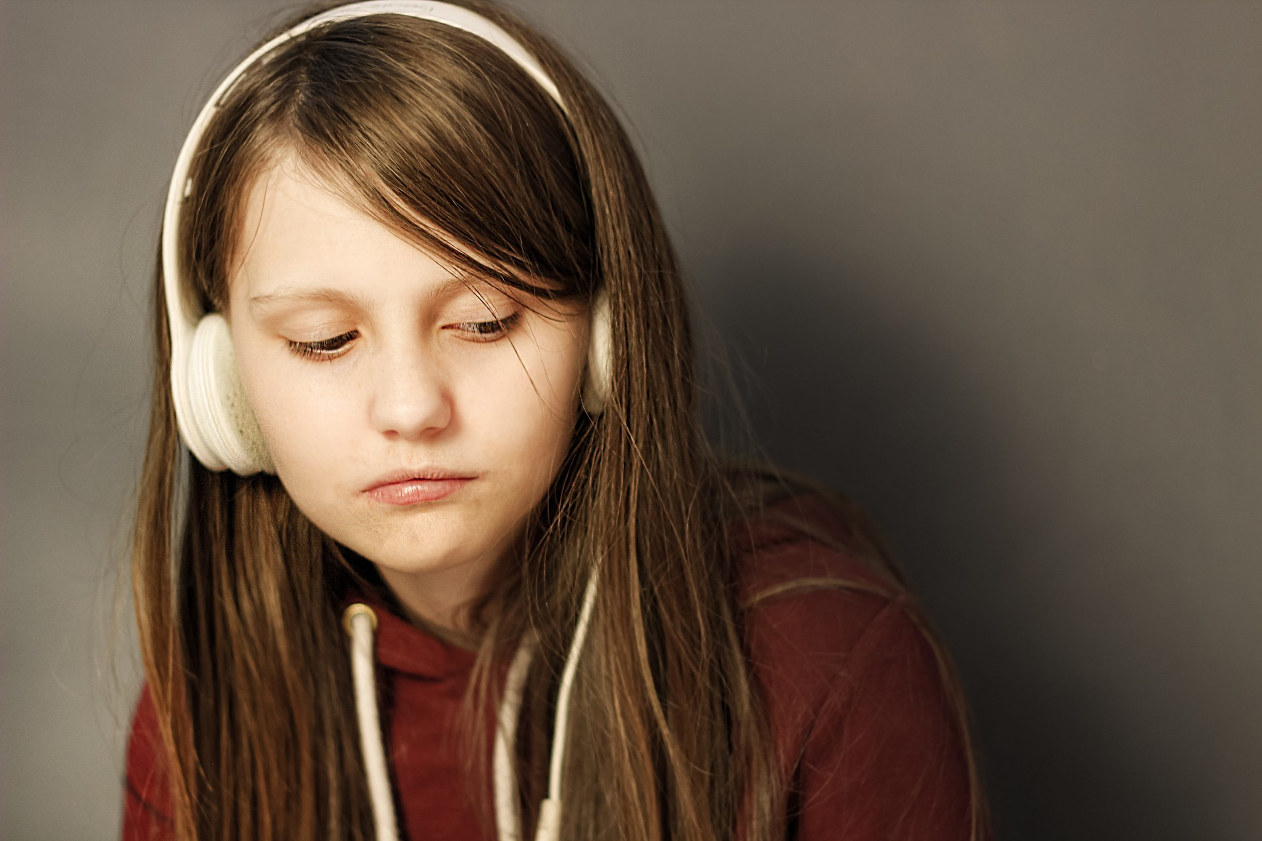 Young girl with dark hair and white headphones on looking sad