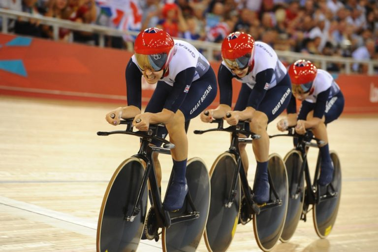 3 Great Britain athletes on bikes with red helmets in a velodrome