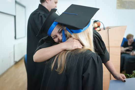 Two women in graduation hats and gowns hugging