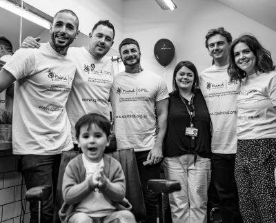 A black and white picture of a group of people wearing CPSL Mind t shirts and a little boy sat in a barbers chair