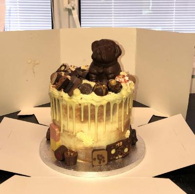 A cake with white chocolate a dark chocolate decoration