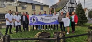 A group of people holding a CPSL Mind banner