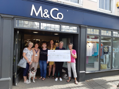 A group of women holding a cheque in front of an M&Co shop