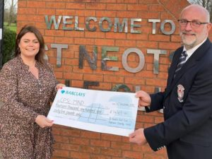 A man and women holding a cheque for CPSL Mind in front of a Welcome to St Neots Golf Club sign on a brick wall