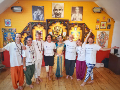 A group of people in CPSL Mind t shirts smiling at the camera in a yellow yoga studio